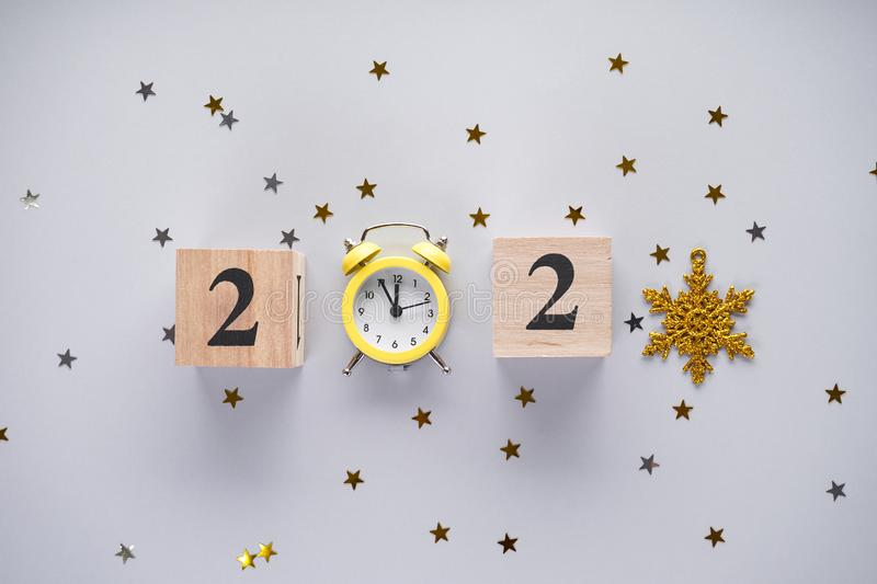 New Year flat lay composition. Christmas decoration and yellow vintage alarm clock with confetti on a gray background.. Christmas royalty free stock photography