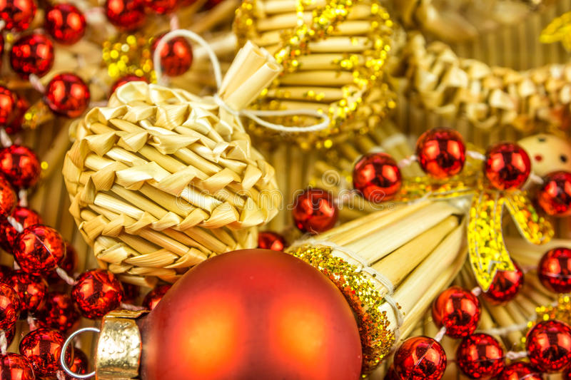 Christmas decorations and background. Christmas decorations, balls, angels, red chain, christmas theme on a mat made of straw royalty free stock image