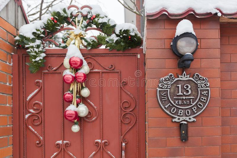 Christmas decorations - balls and spruce branches, over the gate to the house. Beautiful house number royalty free stock photography
