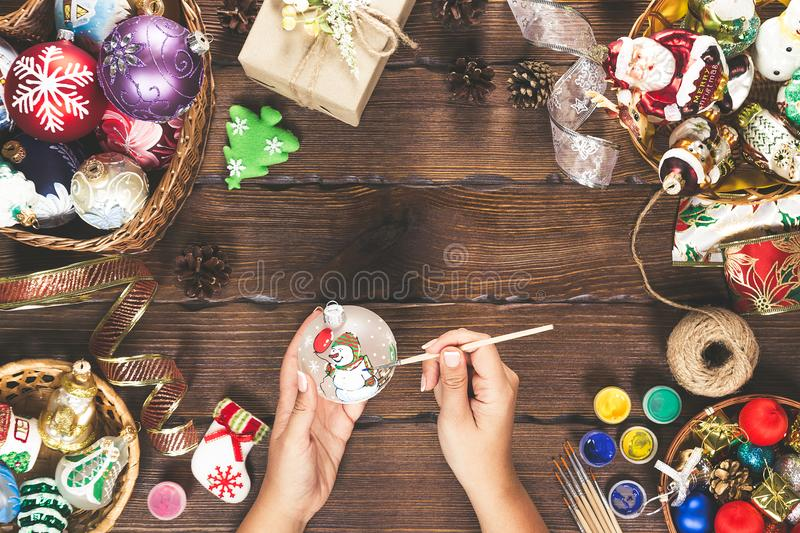 Christmas decorations, balls, toy and gift boxes on old wooden board. Female hands draw New Year decorations. Beautiful frame with stock photo