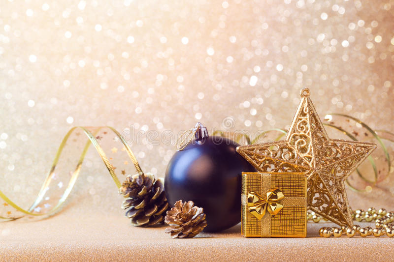 Christmas decorations in black and gold over glitter background. Christmas decorations in black and gold over glitter sparkle background stock images