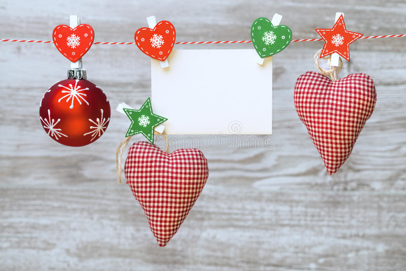 Christmas decorations and blank card, space for your Christmas g. Red textile hearts, Christmas bauble and greeting card with text space, all hanging on a rope royalty free stock photography
