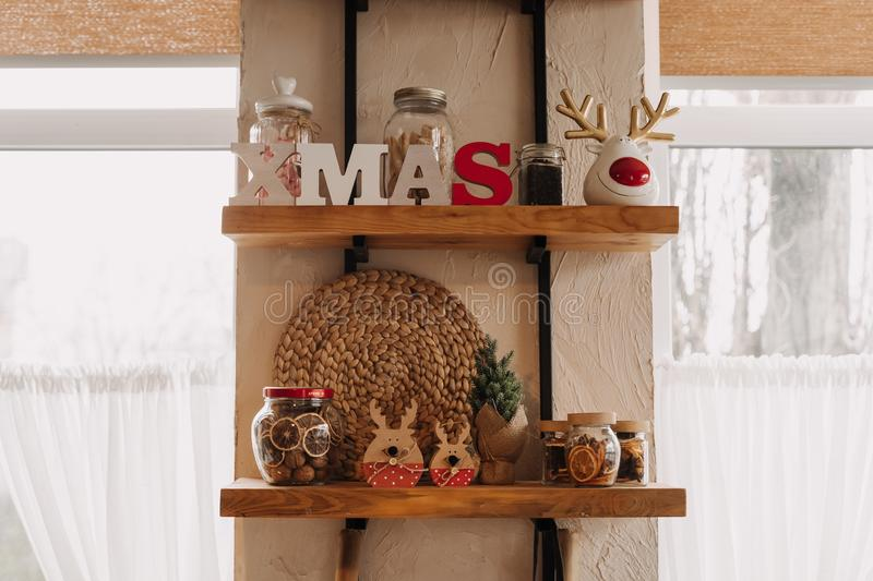 Christmas Decorations and Bottles on Wooden Shelf. Glass Containers with Candies, Dried Citrus and Nuts, Wicker Ornament and Ceramic Statuette in Form of Deer stock image