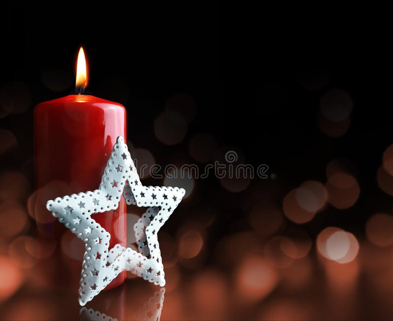 Christmas decorations and burning candle. stock photo