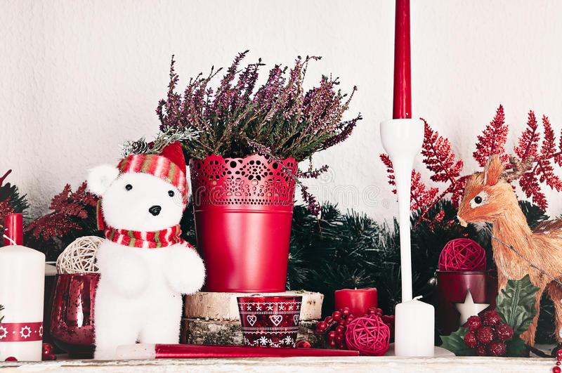 Christmas decorations with candles on a shelf. Christmas decorations with candles, flowers and toys on mantelpiece royalty free stock images
