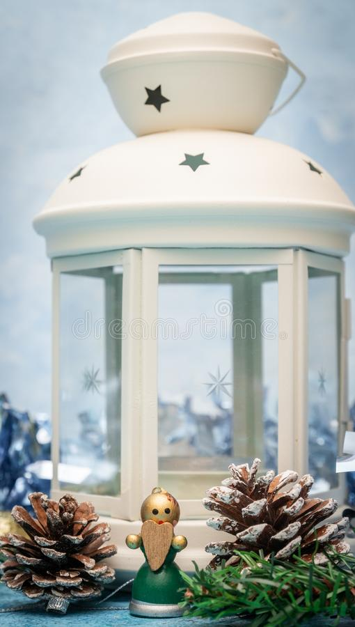 Christmas decorations. Candlestick candle close-up with a small wooden angel with a heart in his hands stock photography