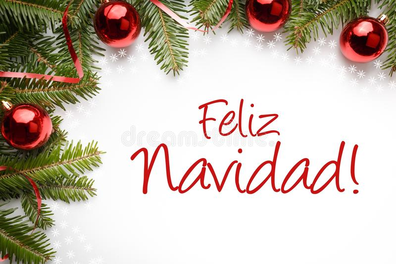 Christmas decorations with Christmas greeting in Spanish `Feliz Navidad!` Merry Christmas!. Decoration made of fir branches and red Christmas ornaments with royalty free stock photo