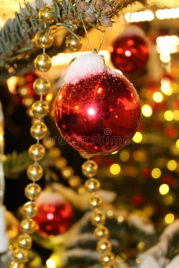 Christmas decorations on the Christmas tree in red and gold colors strewn with lights, close-up. stock photography