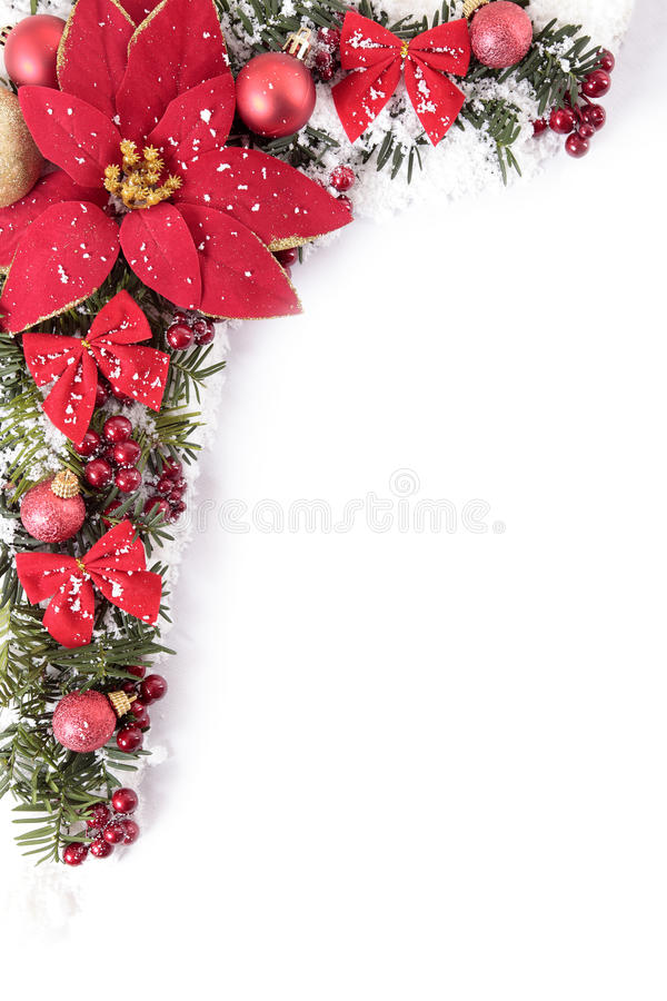 Christmas decorations corner border frame with poinsettia and white copy space, vertical. Christmas border with traditional decorations and poinsttia. Space for royalty free stock photo