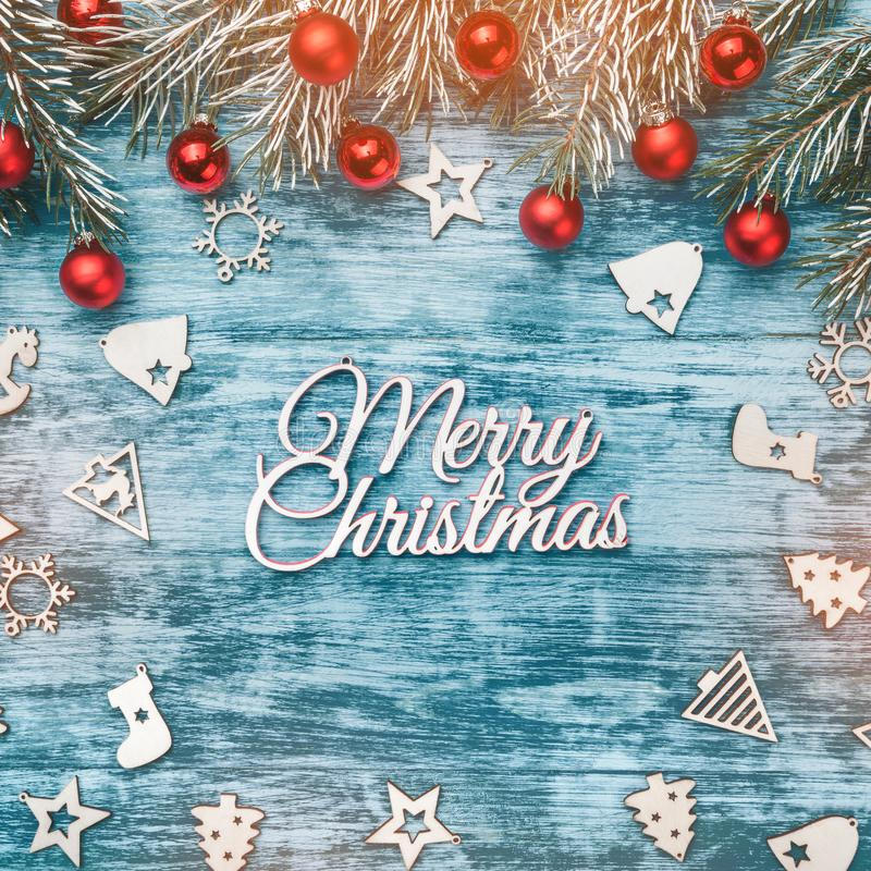 Christmas decorations, fir branches with shiny red baubles and ornamented toys on a blue wooden background. Top view royalty free stock image