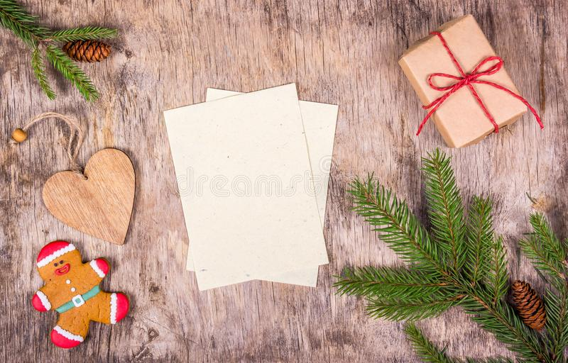 Christmas decorations with fir tree, gift box, gingerbread on wooden board. Gingerbread Man and wooden heart. stock image