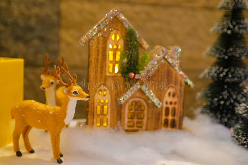 Christmas Decorations, Fluffy Reindeer, Tiny Wooden and Lighted Cottage royalty free stock image