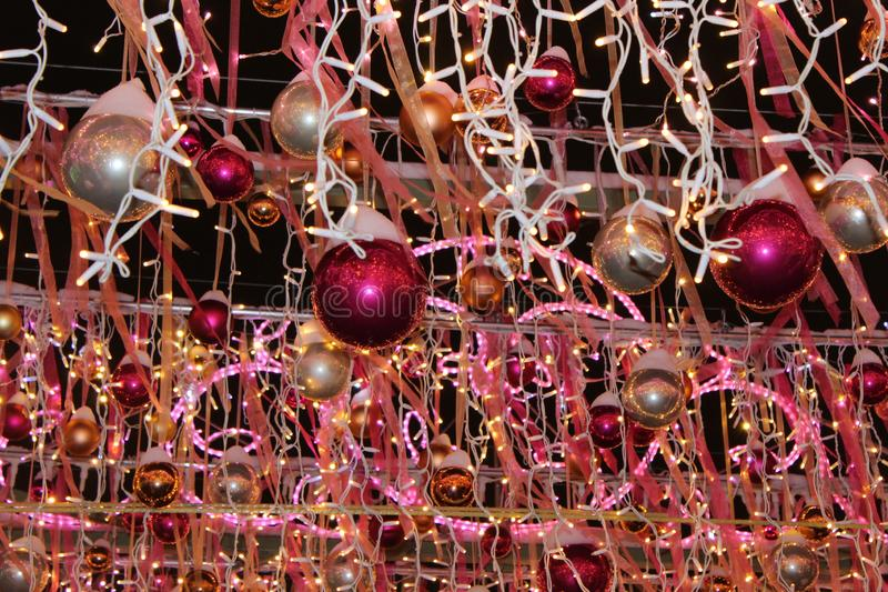 Christmas decorations in the form of balls of red, silver and gold color with lights garlands in the installations on a black back. Christmas decorations in the royalty free stock photo