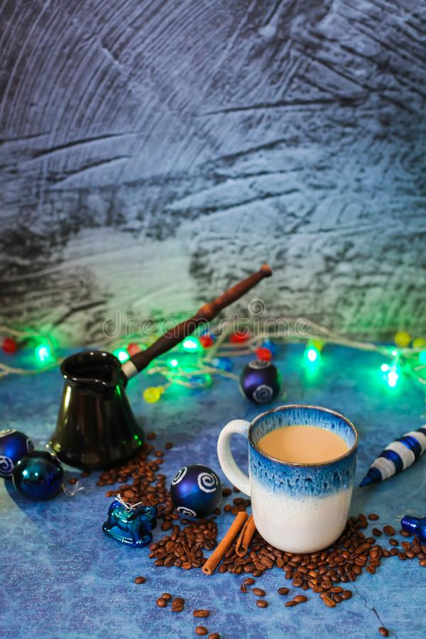 Christmas decorations garland cup of coffee with milk cinnamon sticks scattered coffee beans and black ceramic Cezve stock photos