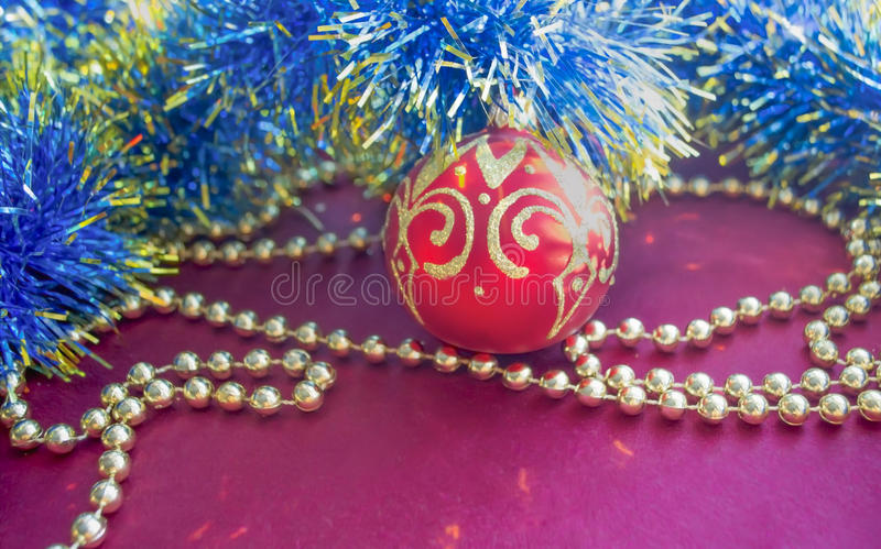 Christmas decorations, golden beads, blue tinsel and red ball with gold pattern, lie on a red background. Christmas decorations: gold necklace, blue and red royalty free stock image