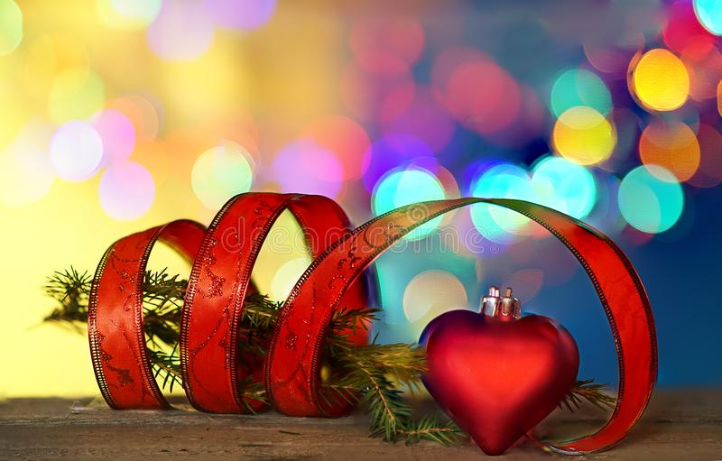Christmas decorations with heart shape, red ribbon under defocused background. Christmas decorations with red ribbon and heart shape , blurred background stock photography