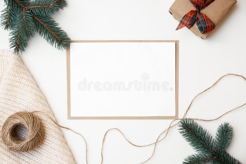 Christmas decorations, knitted scarf, pine bench, twine, craft envelope, blank greeting card with copy space for your text. Xmas. Composition for your banner or stock images