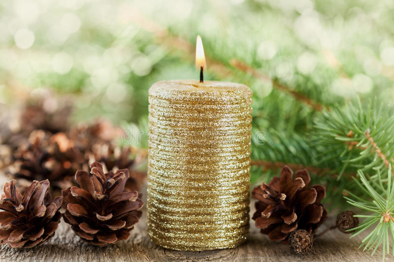 Christmas decorations with lighted candle, pine cones and fir branches on wooden background with magic bokeh effect, Christmas car. D with copy space for your stock images