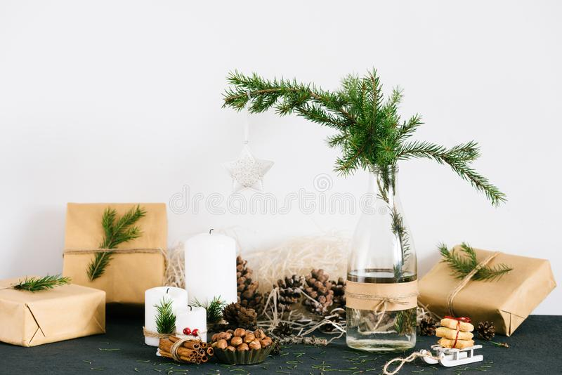 Christmas decorations with lit candles, gift boxes and spruce in the bottle on the table 库存照片