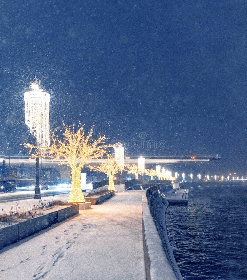 Christmas decorations on Moskvoretskaya embankment. Night illumination. Lanterns wine glasses and golden trees. Snowy night. stock photos