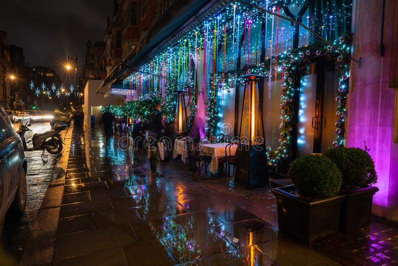 Christmas decorations on Mount Street in Mayfair, London. LONDON - DECEMBER 23, 2018: Shops and restaurands on Mount Street in Mayfair, luxury shopping district royalty free stock images