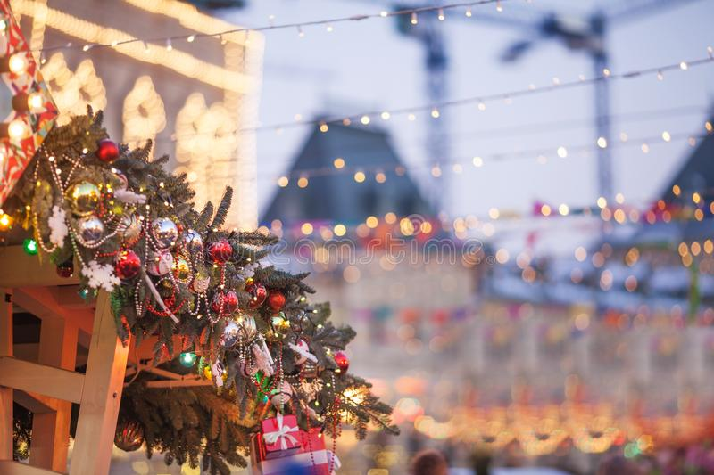 Christmas decorations and New Year tree with colorful lights on a city street during the festive winter fair. Concept of christmas royalty free stock photo
