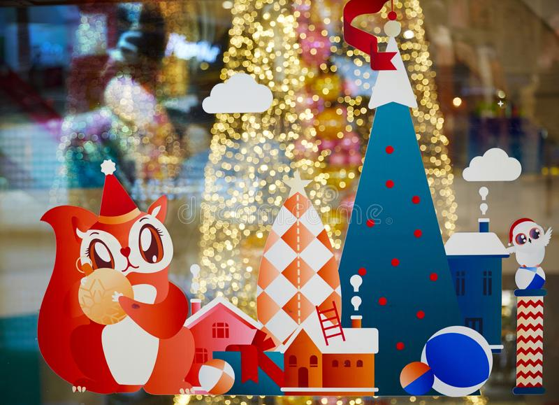 Christmas decorations Papercuts. Paper cut of snow house, Christmas tree, squirrel and gifts, yellow bokeh defocused blurred lights and sparkles abstract in royalty free stock photography