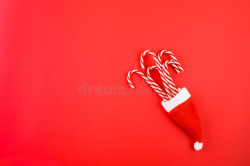Christmas decorations on a red background. Christmas or New Year background. Gift box, candy caramel cane and   decorations on red background. Christmas holiday royalty free stock image