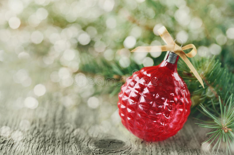 Christmas decorations with red Christmas ball and fir branches on wooden background with magic bokeh effect, Christmas card with. Copy space for your text or royalty free stock photos