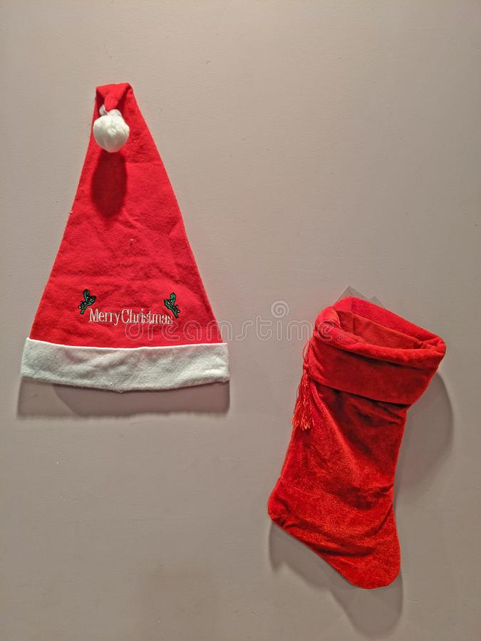 Red and white hat with Merry Christmas and red stocking stock images