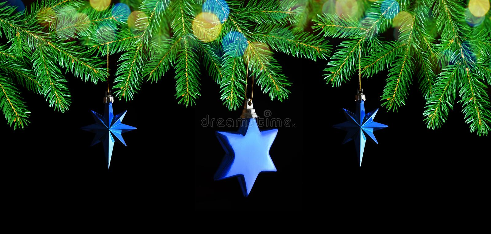 Christmas decorations in the shape star hanging on fir branch. stock photography