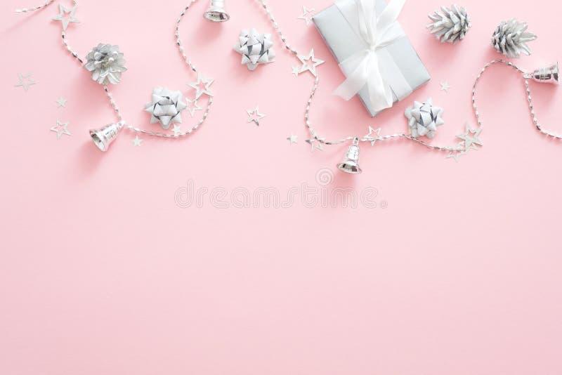 Christmas decorations, stylish silver gift box, pine cones, ribbon, confetti on pastel pink background. Minimal flat lay style stock image