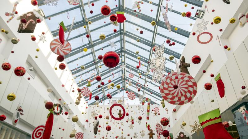 Christmas decorations and toys hang on thin threads. Abstract background of New Year`s decor in the mall, airport or station room stock photo