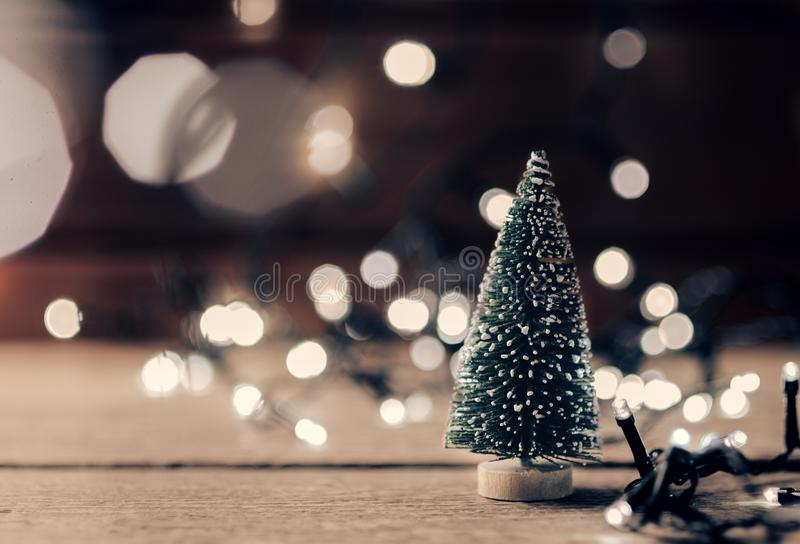 Christmas decorations on wooden table with glowing lights. A small artificial Christmas tree and an electric garland. stock photos