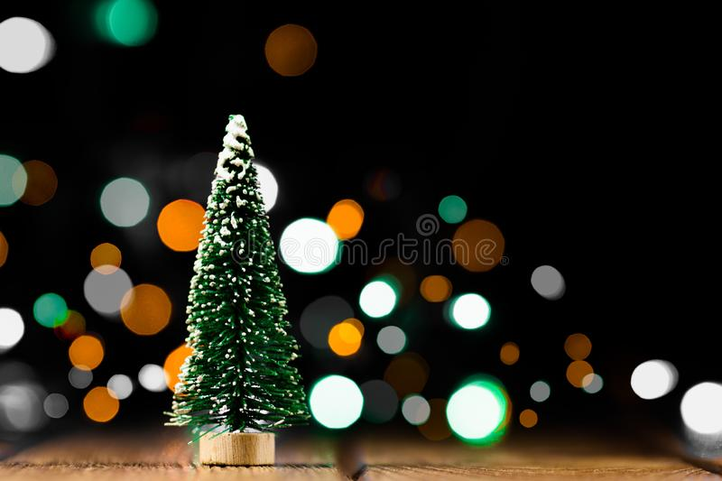 Christmas decorations on a wooden table with glowing lights. A small artificial Christmas tree with light bokeh background stock photos