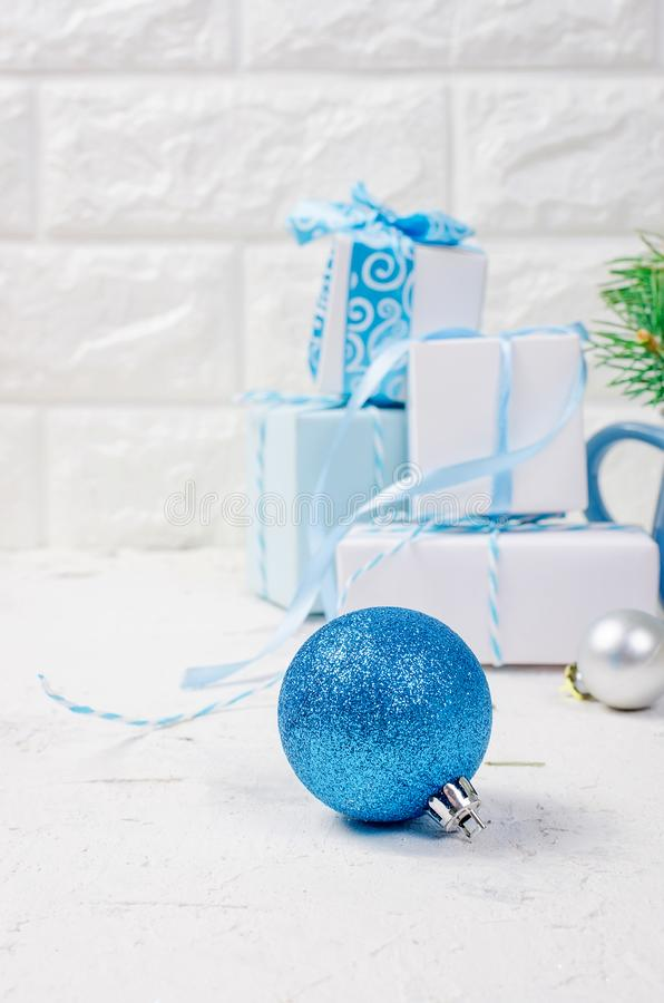 Christmas decorative background with fir branches, cones, silver and blue christmas ball and tojs, gifts and ribbinon the white stock photo