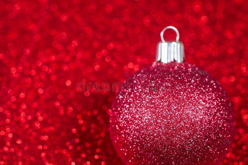Christmas decorative ball on glitter bokeh. Christmas decorative red ball on glitter bokeh background. Christmas background royalty free stock image