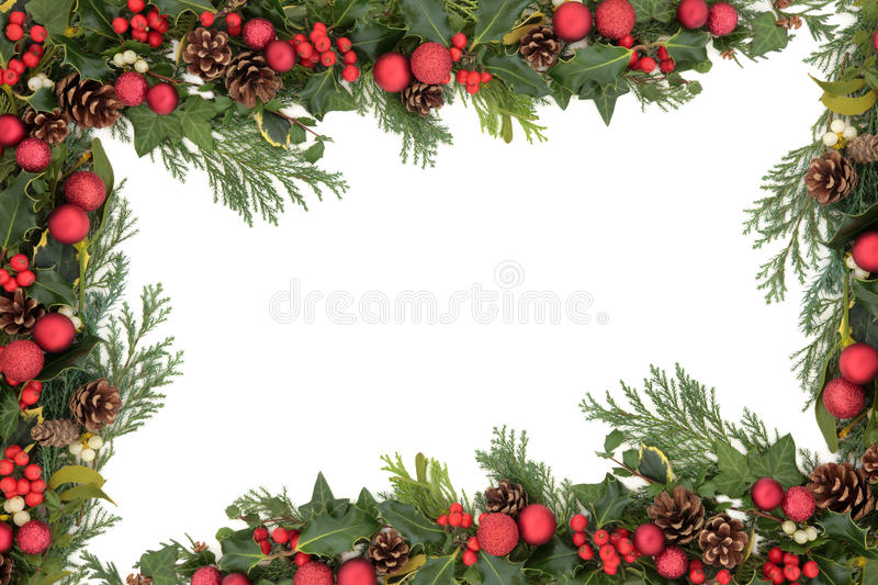 Christmas Decorative Border. Christmas background floral border with red baubles, natural holly, mistletoe, ivy, fir leaf sprigs and pine cones over white royalty free stock image