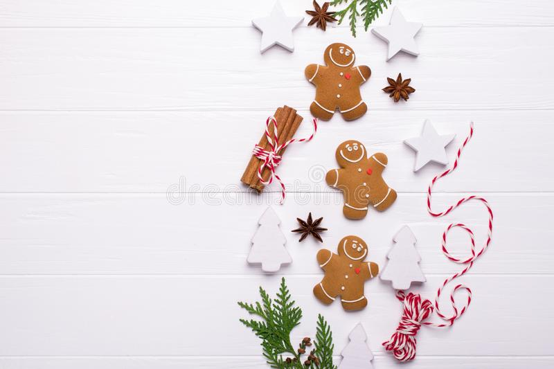 Christmas Decorative Border made of Festive Elements. Smiling gingerbread man, christmas white decorations, pine branches. royalty free stock image