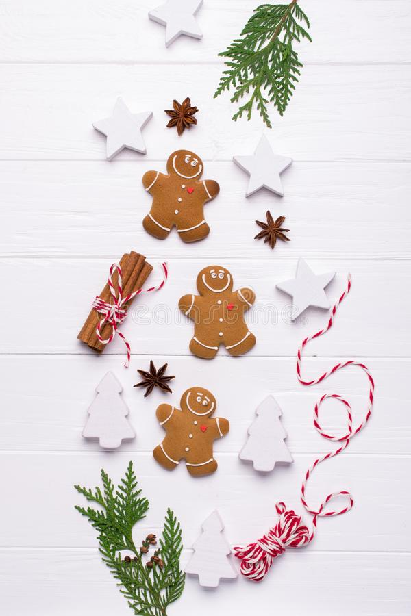 Christmas Decorative Border made of Festive Elements. Smiling gingerbread man, christmas white decorations, pine branches. Flat lay, top view royalty free stock photography