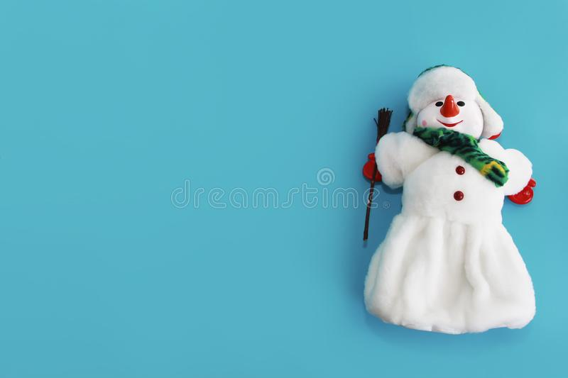 Christmas decorative toy snowman in a white fur coat and hat on a blue background for the New Year holiday stock photo