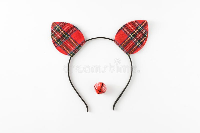 Christmas deer funny face made of red ears hat and little red tambourine isolated on white. New year celebration concept. royalty free stock photo
