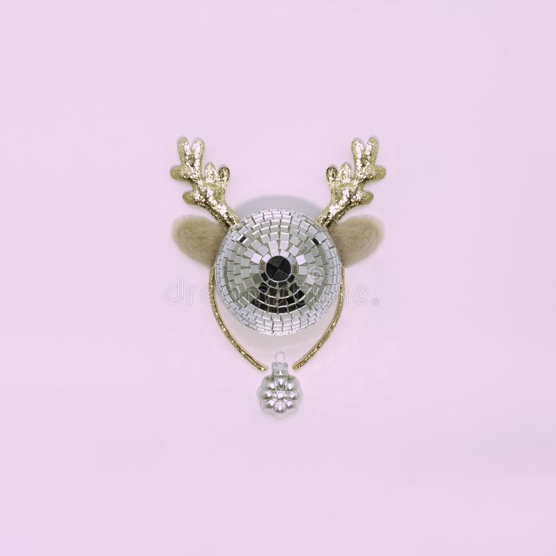 Christmas deer on a pink background made of disco ball and decorative deer horns. View from above. The concept of a winter vacatio royalty free stock image