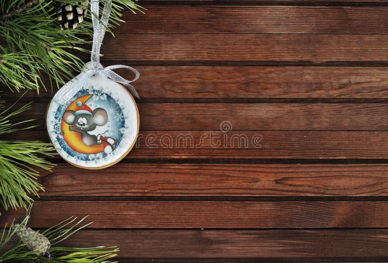 Christmas delicious gingerbread Christmas ball with a mouse on a wooden background with branches of spruce with an empty space und stock photography