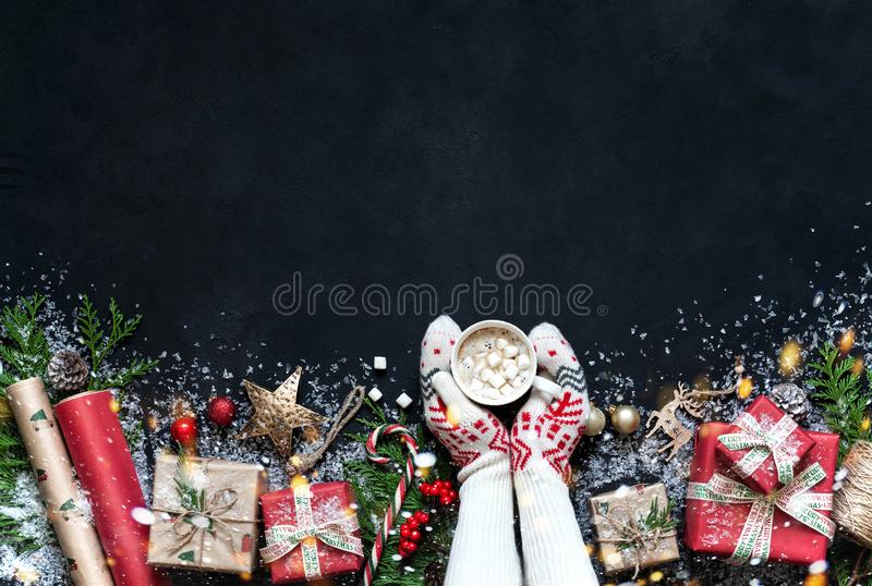 Christmas composition on a black background Christmas decorations, boxes, branches of tree, cap, Santa, star. royalty free stock photo