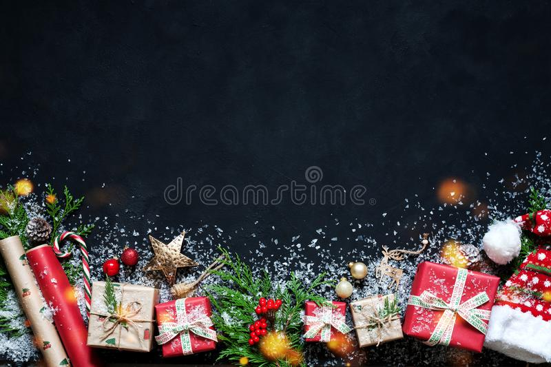 Christmas composition on a black background Christmas decorations, boxes, branches of tree, cap, Santa, star. Christmas design with Nativity. Christmas royalty free stock photography