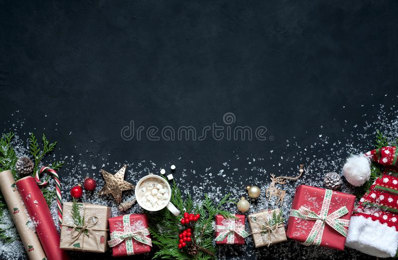 Christmas composition on a black background Christmas decorations, boxes, branches of tree, cap, Santa, star. stock photos
