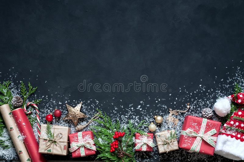 Christmas composition on a black background Christmas decorations, boxes, branches of tree, cap, Santa, star. royalty free stock image