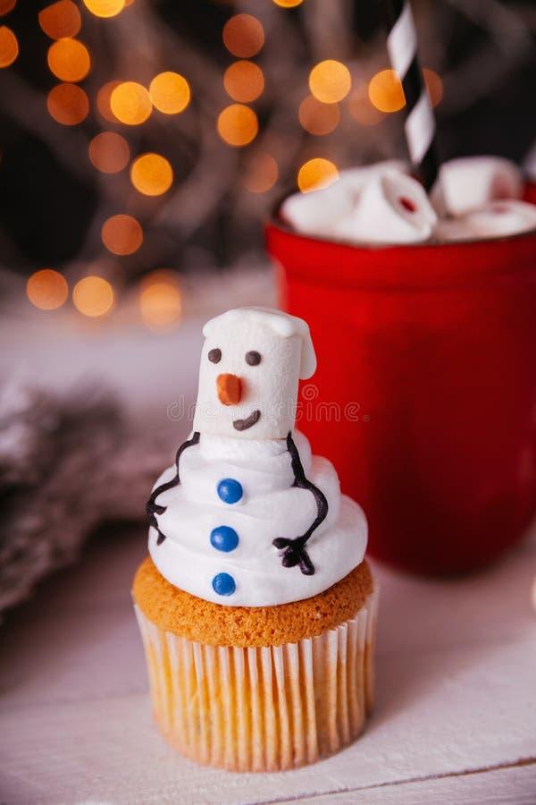 Christmas Dessert. Snowman Cupcake And Mug Of Hot Chocolate Behind royalty free stock photography