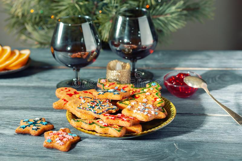 Christmas dessert - a traditional cookie on the background of a green Christmas tree. Two glasses and a candle on a wooden table stock images
